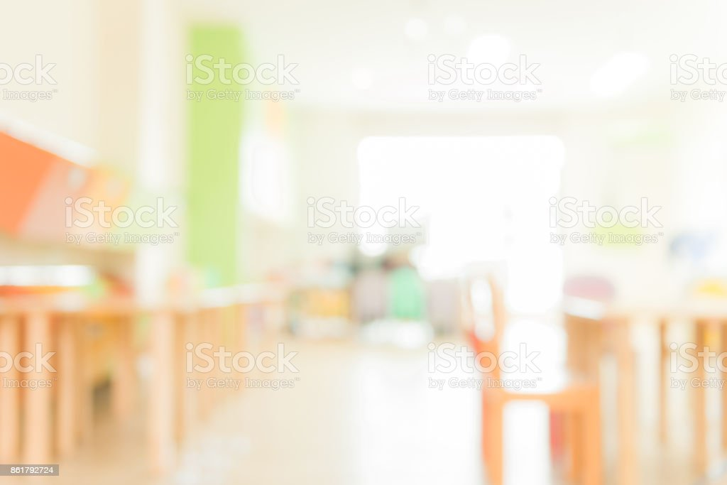 School classroom in blur background without young student; Blurry view of elementary class room no kid or teacher with chairs and tables in campus. Vintage effect style pictures. stock photo