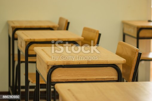 1047047834 istock photo School classroom with desks chair wood, and greenboard in high school thailand, vintage tone education concept 886280930