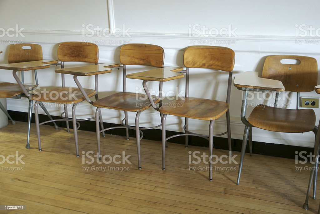 School Classroom with Row of Empty Old-Fashioned Desk Chairs royalty-free stock photo