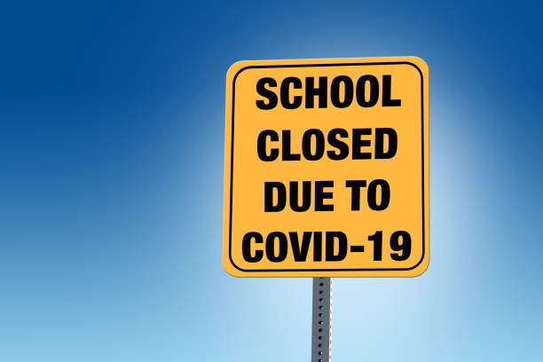 School Closed Due to COVID-19 sign with blue background stock photo