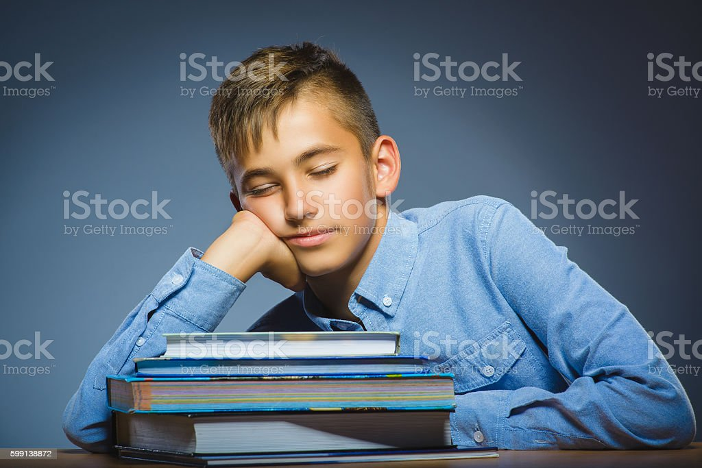 school concept. Closeup portrait boy asleep on pile of books stock photo