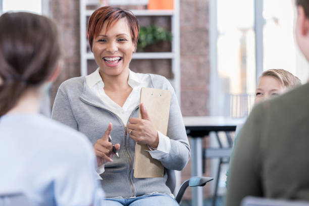 School counselor filitates discussion group Confident mid adult female school counselor talks with a group of students. school counselor stock pictures, royalty-free photos & images