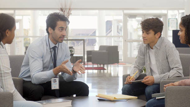 School counselor in discussion with students A mid adult male school counselor sits in his school lobby with a few students and gestures as he speaks. school counselor stock pictures, royalty-free photos & images