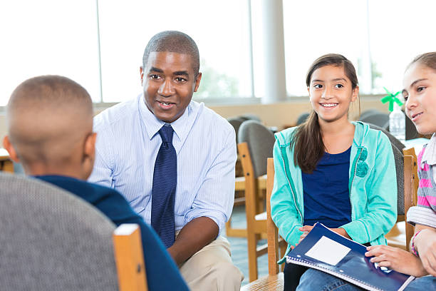 School counselor meeting with group of diverse elementary students Mid adult African American man is school counselor or teacher. He is meeting with diverse group of elementary age students. Children are participating in group therapy or counseling session, and are smiling while learning. school counselor stock pictures, royalty-free photos & images