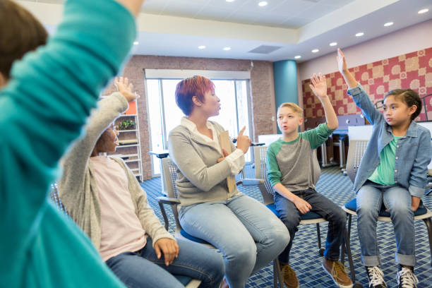 school counselor talks with group of elementary students - school counselor stock pictures, royalty-free photos & images