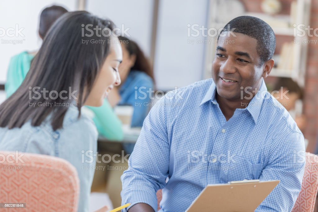 School counselor talks with student stock photo