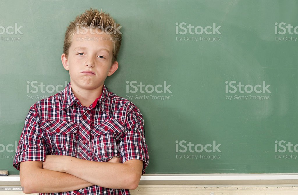 School Days: Bored Kid at Chalkboard with Copyspace stock photo