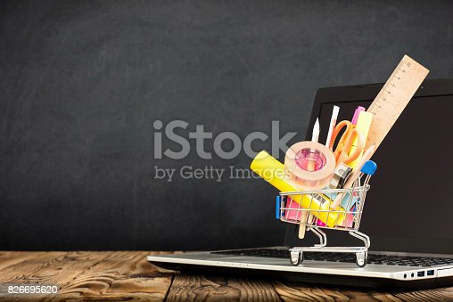 istock School Desk, Pencils And Various Supplies In Metal Shopping Holder On Laptop With Blackboard Background 826695620