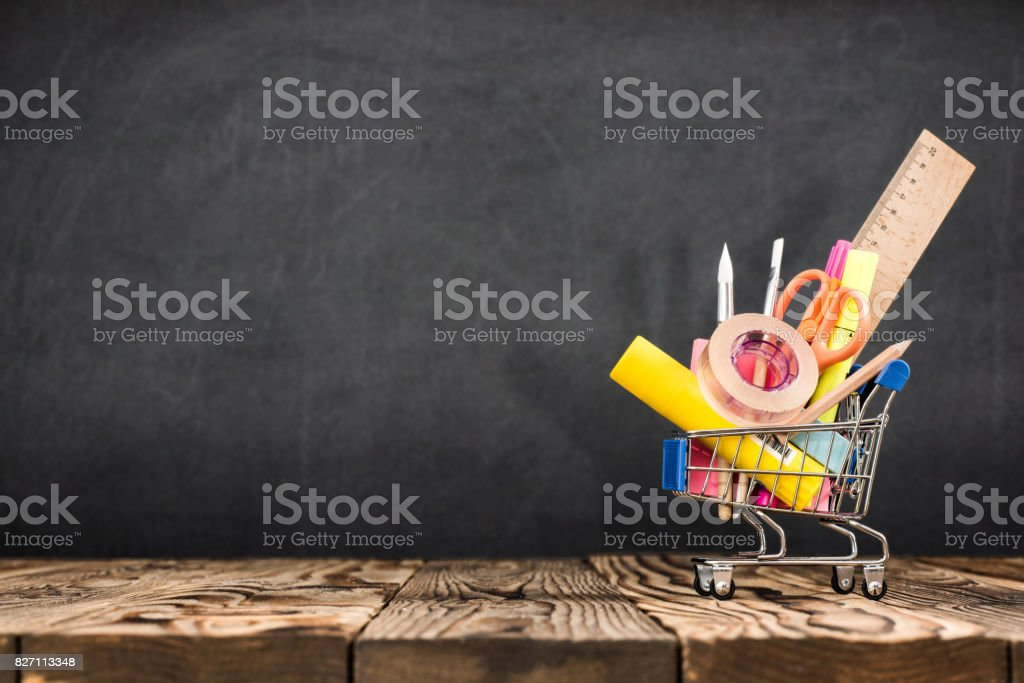 School Desk, Pencils And Various Supplies In Metal Shopping Holder On Blackboard Background stock photo
