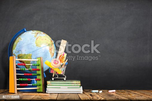 istock School Desk, Pencils And Various Supplies In Metal Shopping Holder On Blackboard Background 827116468