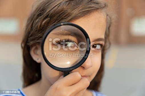 young girl in a school yard, holding a magnifying glass, looking through it