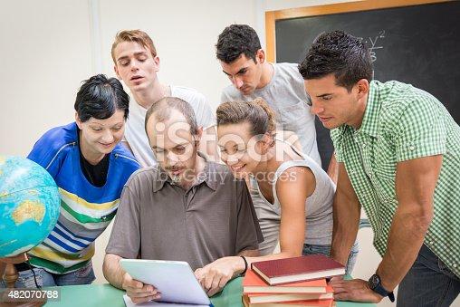 485539628 istock photo School education scene: students and teacher using tablet 482070788