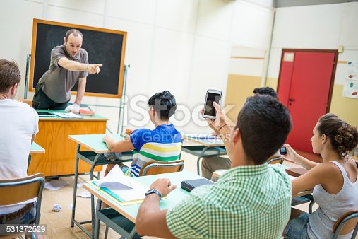 485539628 istock photo School education scene: students in class with smartphones 531372529