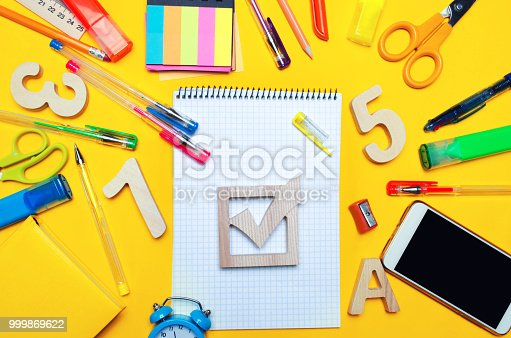 istock school elections concept. Election check box and school accessories on a desk on a yellow background. education. stationery, watches, colored pens, phone, markers. notebook. view from above. copy space. top view. flat lay 999869622