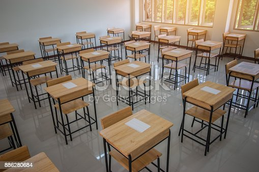 1047047834 istock photo School empty classroom with test sheet or exams paper on desks chair wood and greenboard at high school thailand, education test concept 886280684