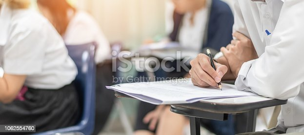 963192098 istock photo School exam student's taking educational test, admission test, thinking hard, writing answer in university classroom, education and world literacy day concept 1062554760