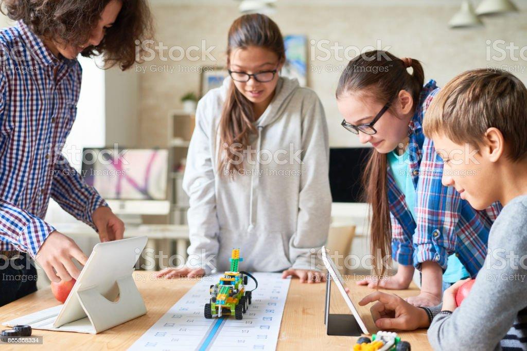 Schulfreunde holding experimentieren mit Spielzeug Fahrzeug – Foto
