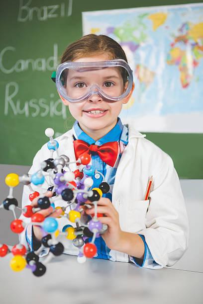 School girl assembling molecule model for science project in lab - foto de acervo