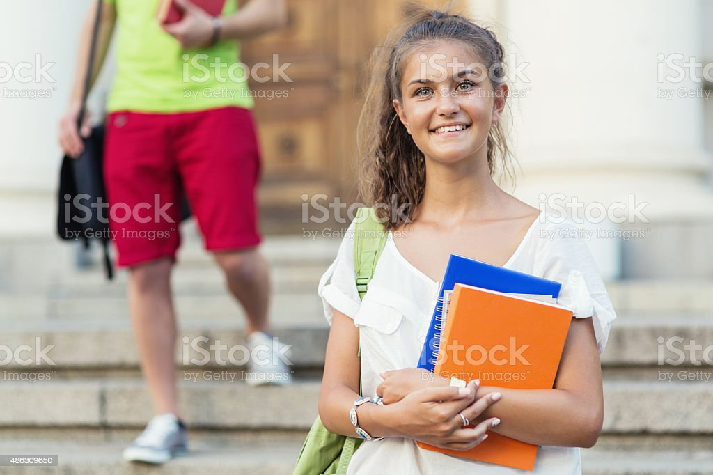 School girl holding textbooks and smiling stock photo