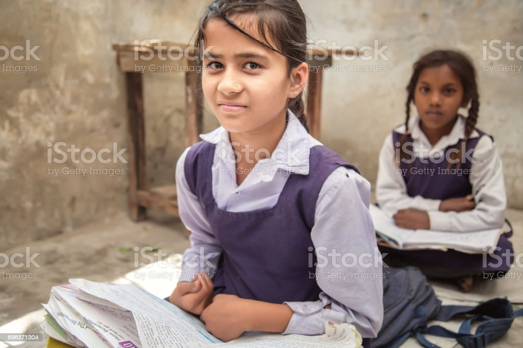 School Girl In Uniform Of Indian Ethnicity Sitting In Their Village Classroom Looking At Camera