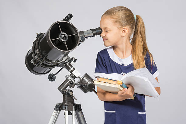 School girl looking through a telescope standing with textbooks stock photo
