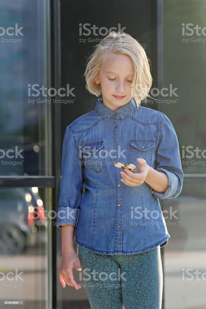 A school girl plays with a gold spinner. A popular toy. stock photo