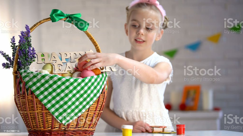 School girl putting colored egg in basket, holiday atmosphere,...