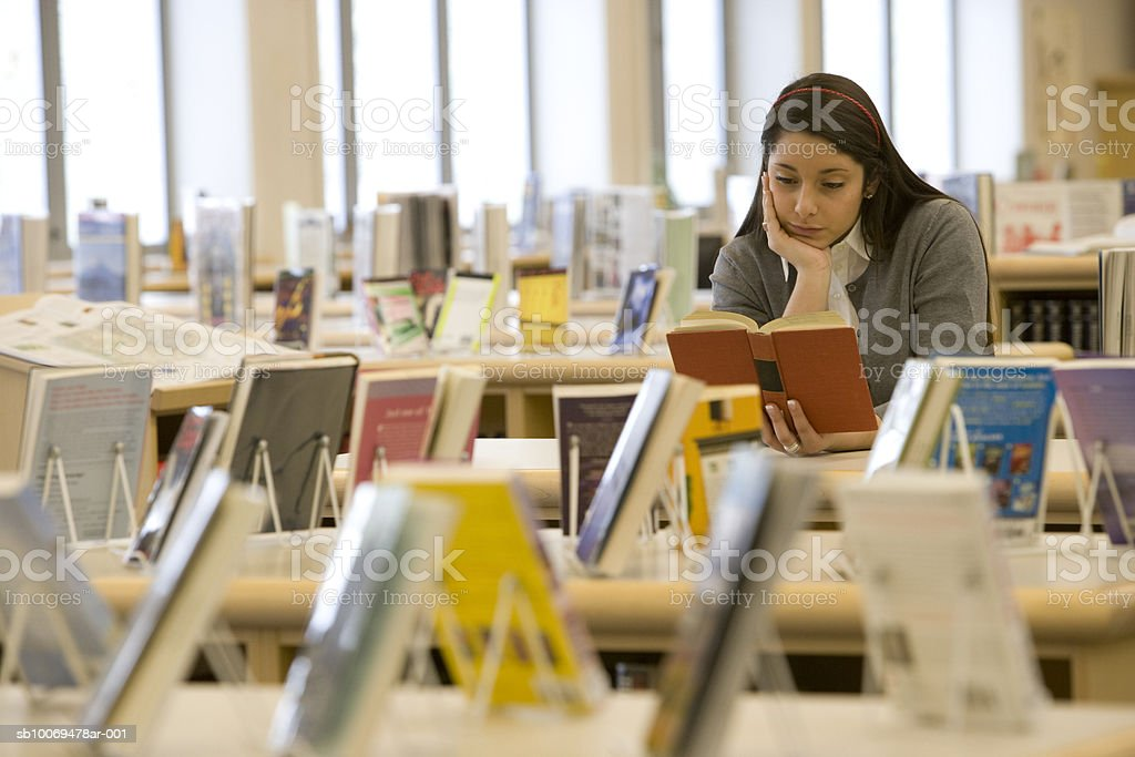 School girl (16-17) reading book in library royalty-free stock photo