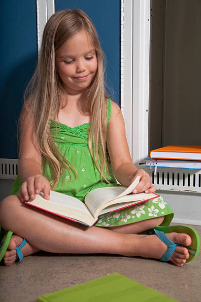School girl reading by locker stock photo