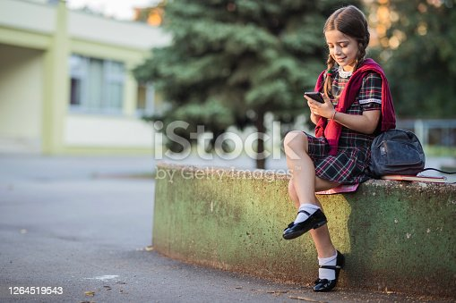 Happy girl sitting in school yard and text messaging