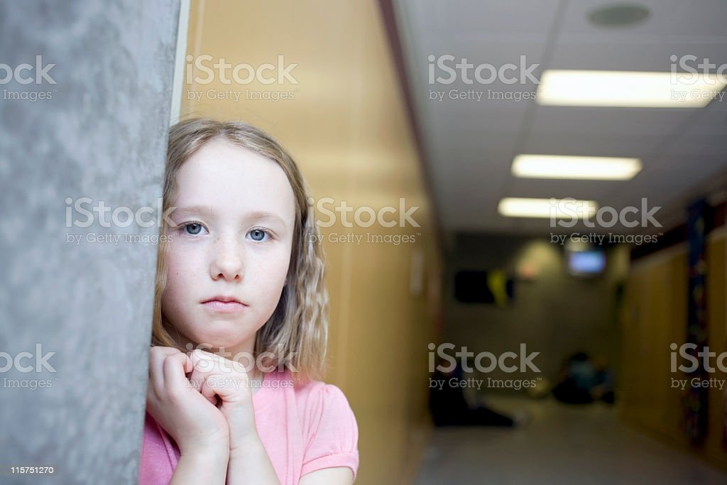 School girl standing at the end of a hallway. stock photo