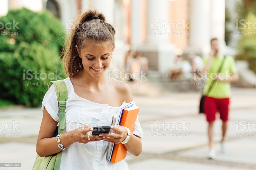School girl texting on a cell phone stock photo