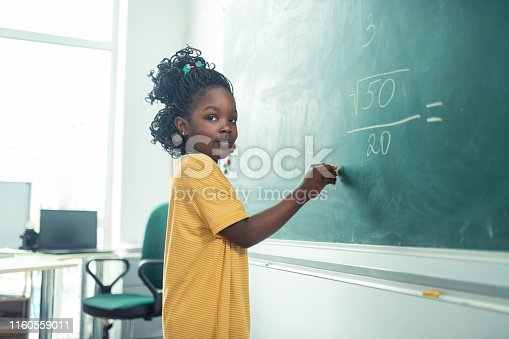 istock School girl thinking what to write on a blackboard. 1160559011