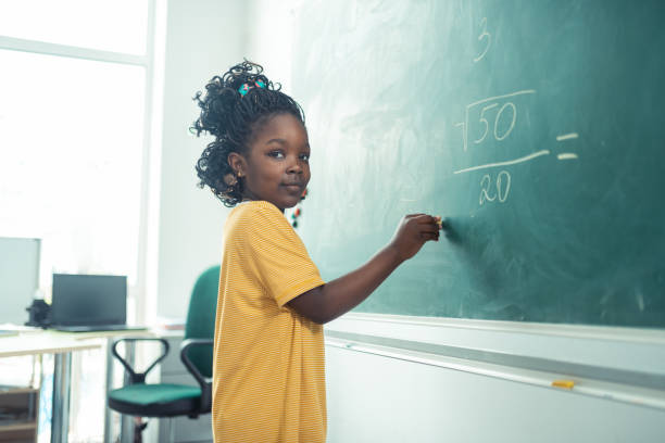 School girl thinking what to write on a blackboard. stock photo