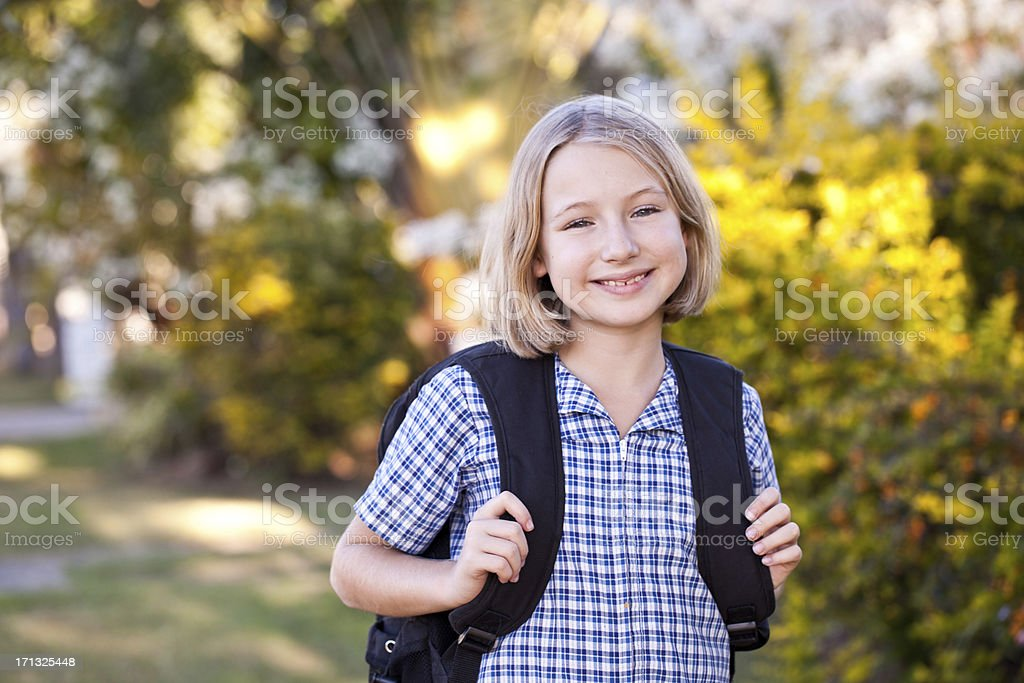 School girl walking home from school with backpack stock photo
