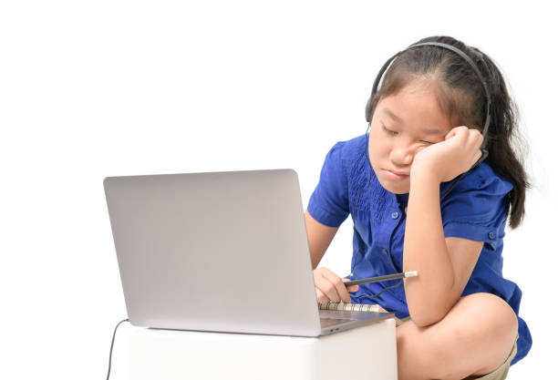 School girl watching online education classes feeling bored and depressed at home. stock photo