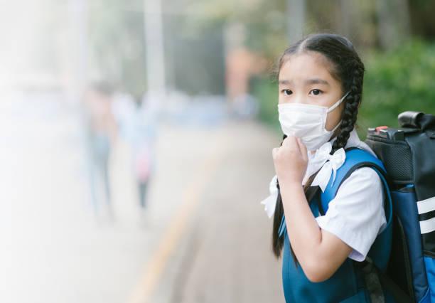 Schulmädchen trägt Mundmaske gegen LuftsmogVerschmutzung in Bangkok Stadt, Thailand – Foto