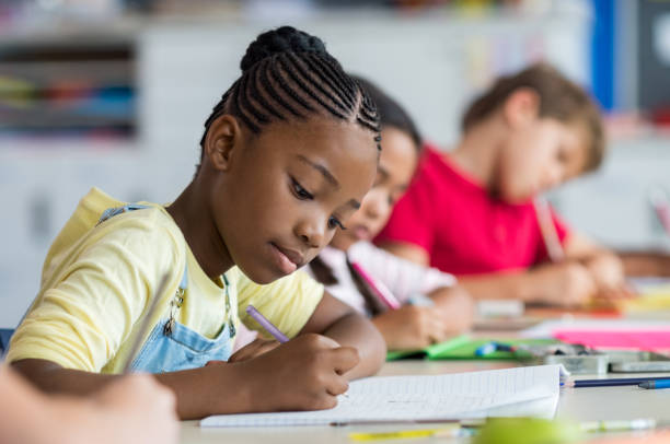 school girl writing in class - school building stock pictures, royalty-free photos & images