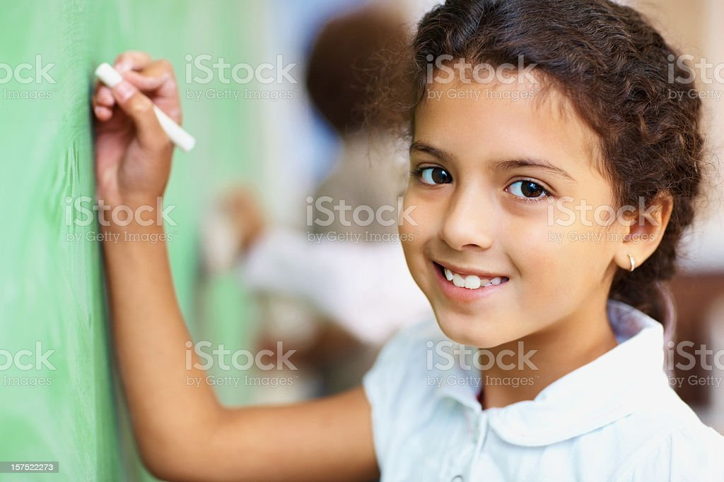 School girl writing on the board with a chalk royalty-free stock photo