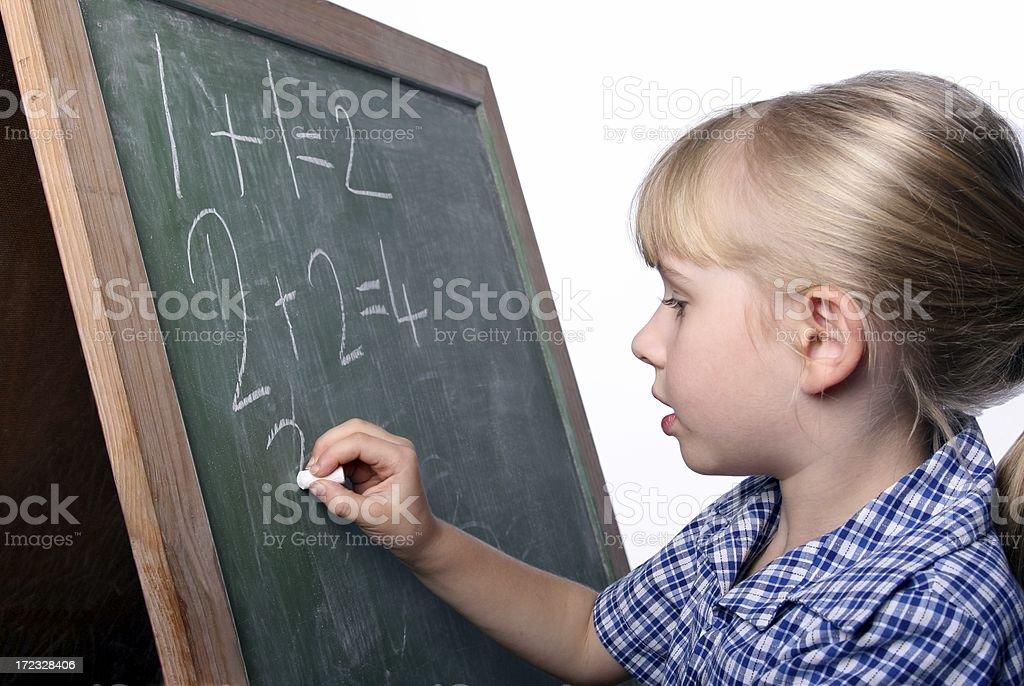 School girl writing sums on blackboard royalty-free stock photo