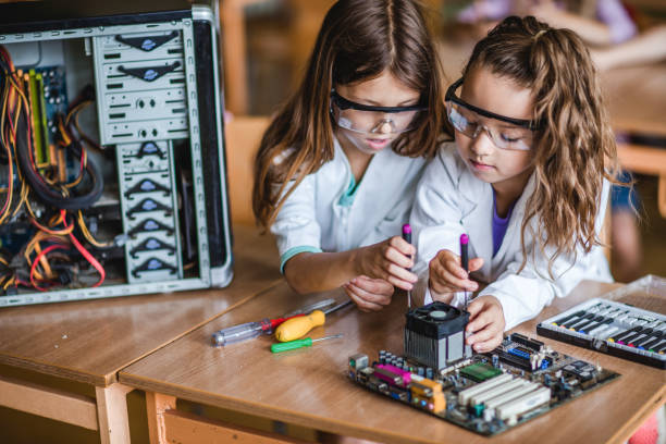 School girls cooperating while repairing mother board in the classroom. stock photo