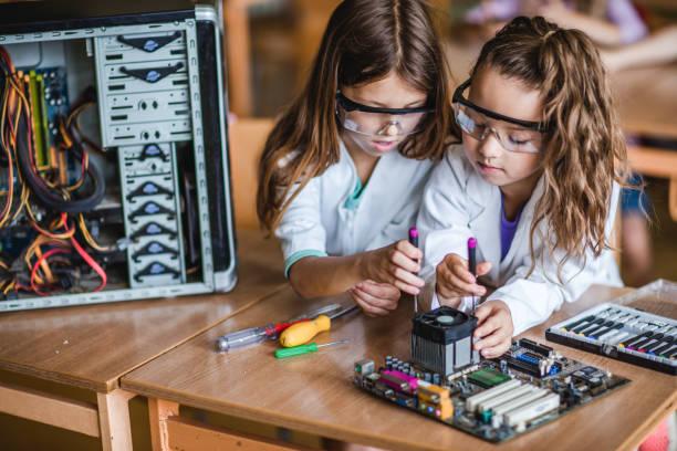 Schulmädchen während der Reparatur Motherboard im Klassenzimmer zusammen. – Foto