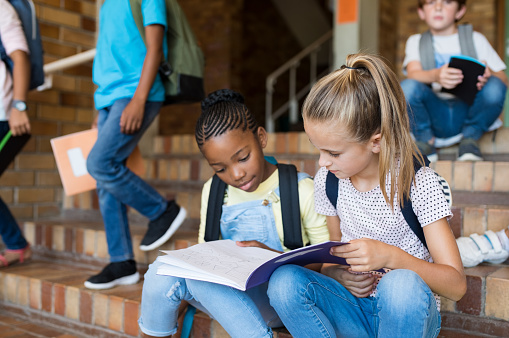 Two young girls sitting together on stairs and studying after school. Elementary schoolgirls studying the notes on copybook. Happy african girl and her friend doing homework on notebook at primary school.