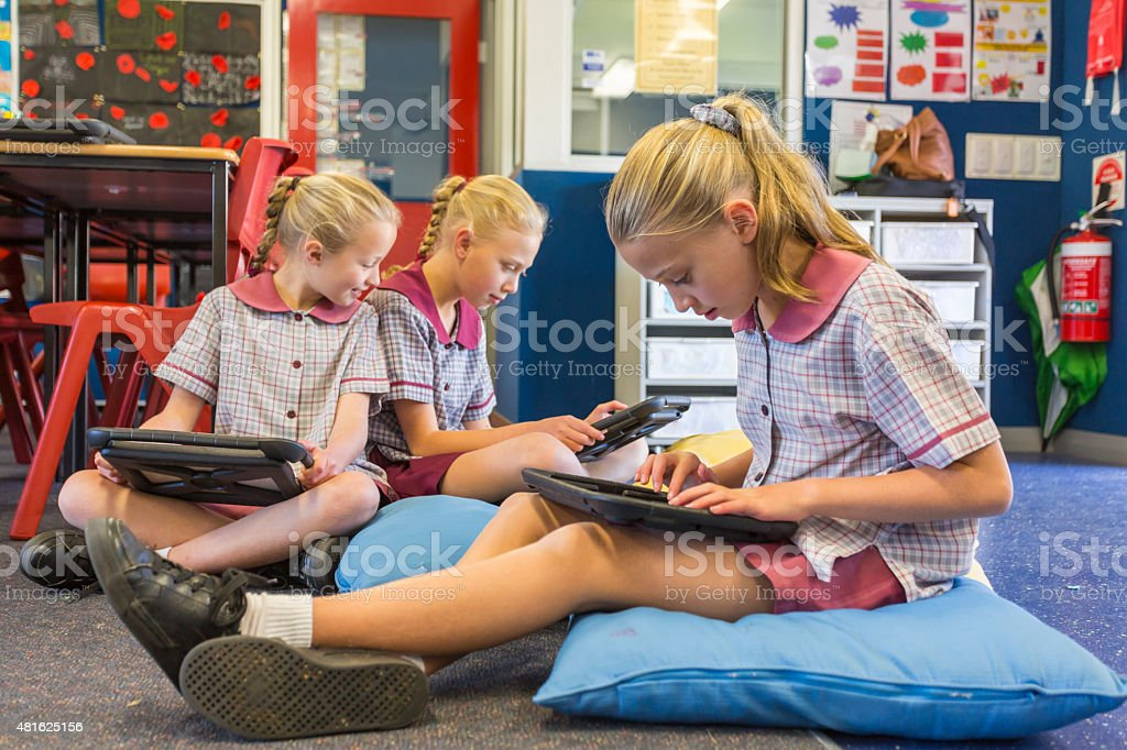 School Girls Using Tablet Computers for Online Learning in Classroom stock photo