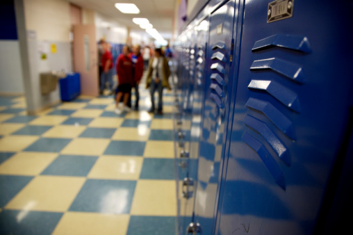 blue school hallway lockers and checkered tile in high school students in the background (down-sampled to increase sharpness)