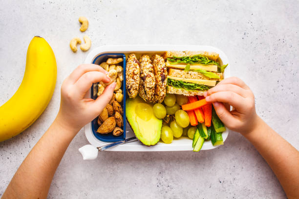 School healthy lunch box with sandwich, cookies, fruits and avocado on white background. stock photo