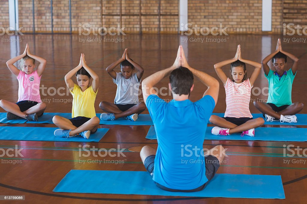 School kids and teacher meditating during yoga class stock photo