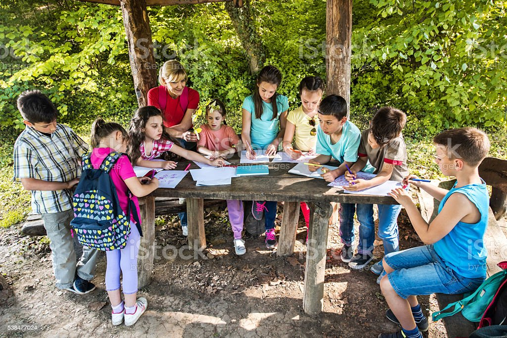 School kids coloring on a field trip with their teacher. stock photo