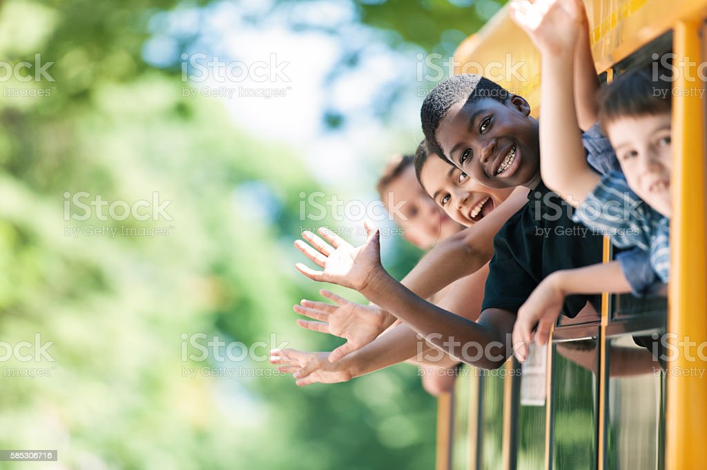 School kids hanging out bus windows - foto de stock