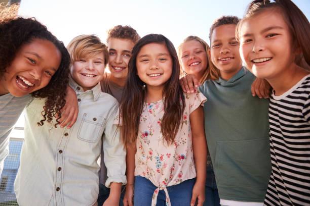 schülerinnen und schüler hängen in pause lächelnd zu kamera - kind vor der pubertät stock-fotos und bilder